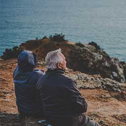 Elderly couple outdoors looking out over a lake