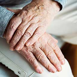 Elderly person crossing their hands over their leg