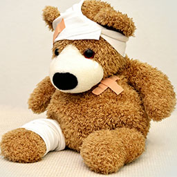 Brown teddy bear with bandages and band-aids