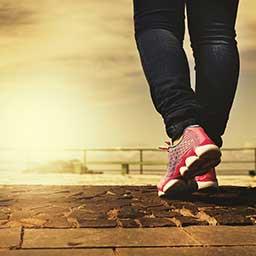 Woman wearing sneakers walking while the sun rises